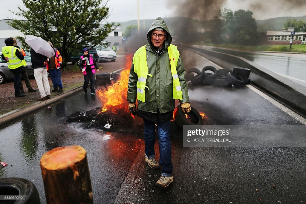 A man walks in front of a fire as protesters block a road to protest against the government's planned labour law reforms, on May 31, 2016 in Saint-Etienne-du-Rouvray, near Rouen, northwestern France. / AFP / CHARLY
