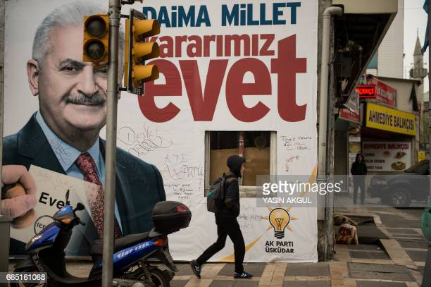 A man walks in front of a giant poster of Turkish Prime Minister Binali Yildirim reading 'forever folk our decision is 'YES' on April 6 2017 in...