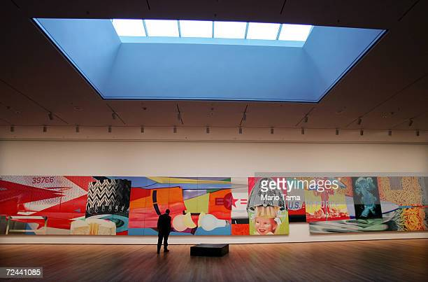A man walks in front of a mural by James Rosenquist titled 'F111' in the newly remodeled Museum of Modern Art during a media preview November 15 2004...