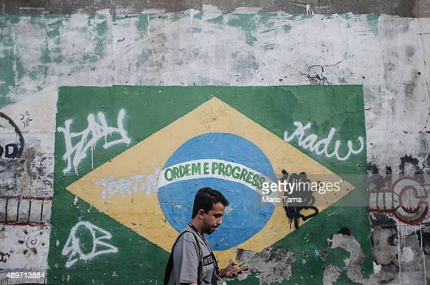A man walks in front of a painted Brazilian flag and other graffiti on a downtown street on September 23 2015 in Rio de Janeiro Brazil The US dollar...