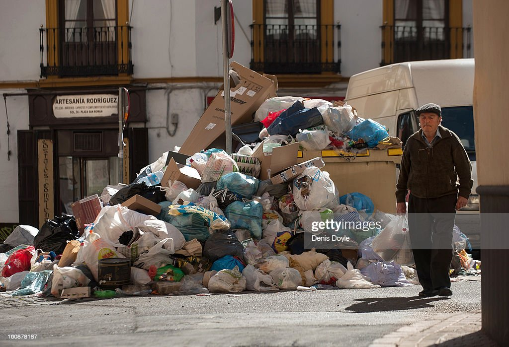 A man walks in front of a pile of uncollected grabage during the 11th day of the waste disposal strike on February 7, 2013 in Seville, Spain. Waste disposal workers are striking over a 5% proposed cut in their salary and an extended working week to 37.5 hours.
