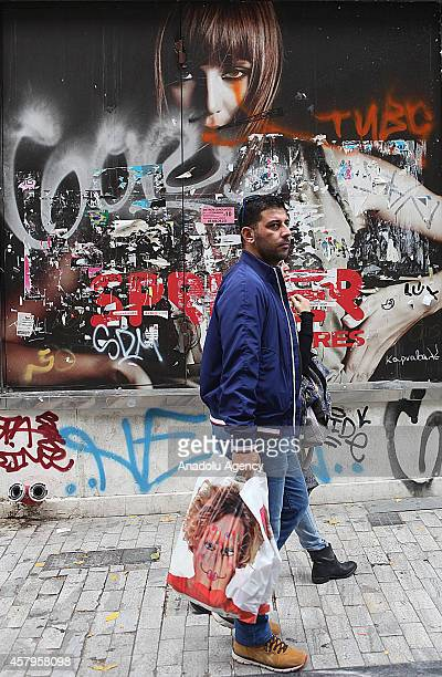 A man walks in front of a shop which is shut down at Ermou street due to the economic crisis in Athens Greece on December 27 2014