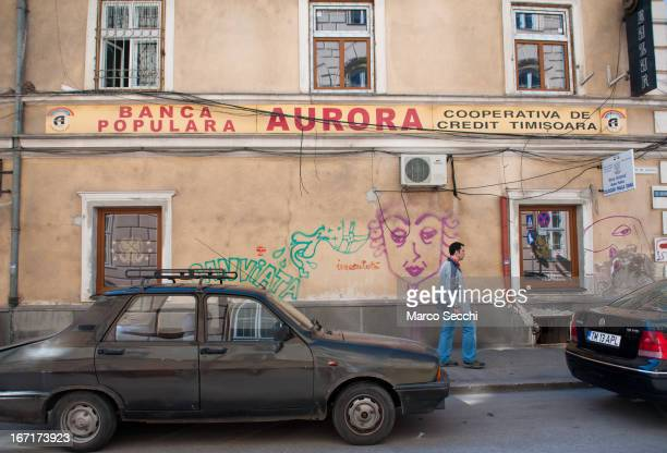 A man walks in front of Banca Populara Aurora on April 14 2013 in Timisoara Romania Romania has abandoned a target deadline of 2015 to switch to the...