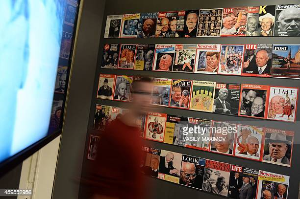 A man walks in front of magazine covers as he visits an exhibition dedicated to the former Soviet leader Nikita Khrushchev in Moscow on November 19...