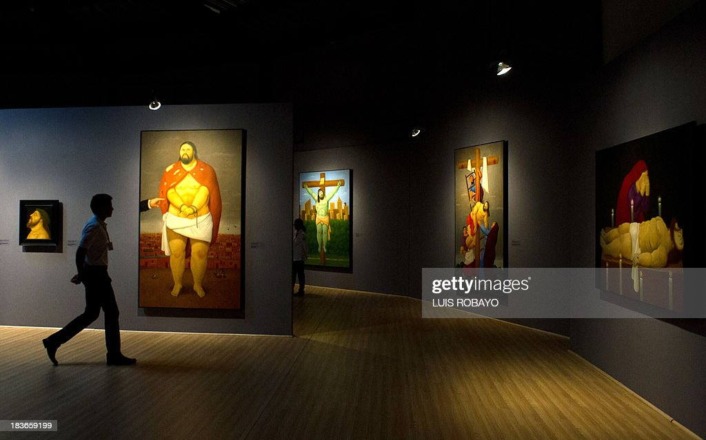 A man walks in front of paintings of the exhibition 'Via Crucis, the passion of Christ' of Colombian artist Fernando Botero, on October 8, 2013, in Cali, department of Valle del Cauca, Colombia. Botero was the curator of his own exhibition, which is composed of 27 oil paintings and 34 drawings combining traditional aspects of Catholicism and the modern world.