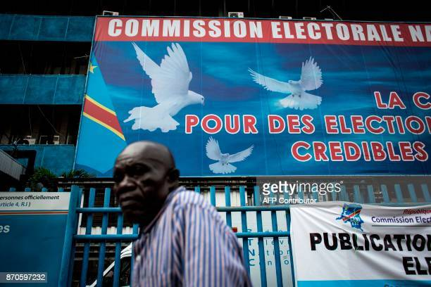 A man walks in front of the Commission Electorale Nationale Independante headquarters on November 05 2017 in Kinshasa following an announcement of...