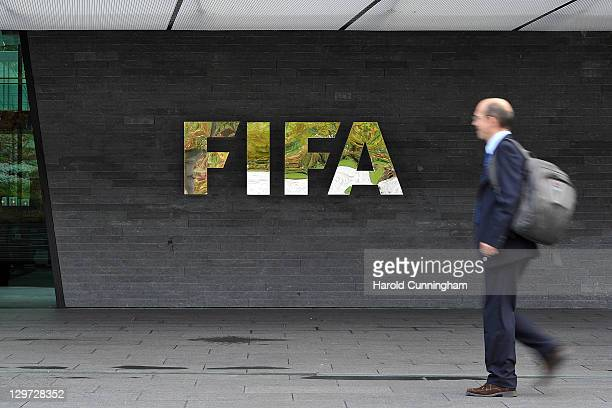 A man walks in front of the FIFA logo displayed outside the FIFA headquarters prior to the FIFA Executive Committee Meeting on October 20 2011 in...