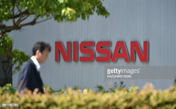 A man walks in front of the logo of Japan's Nissan Motor Corporation at its global headquarters in Yokohama Kanagawa prefecture on May 11 2017 Nissan...