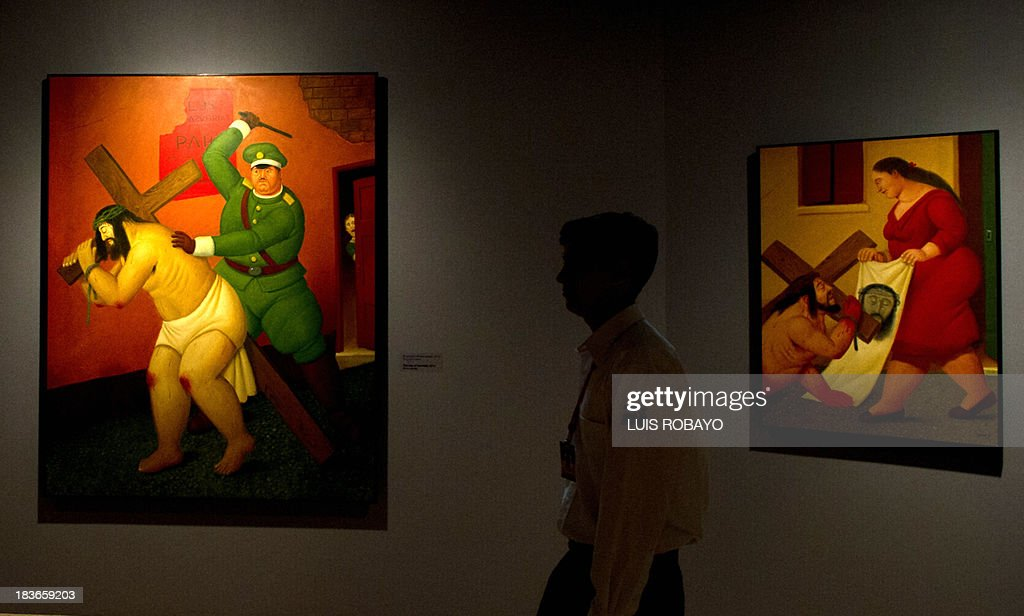 A man walks in front of the paintings 'The way of sorrows' (L) and 'Jesus and Veronica' of the exhibition 'Via Crucis, the passion of Christ' of Colombian artist Fernando Botero, on October 8, 2013, in Cali, department of Valle del Cauca, Colombia. Botero was the curator of his own exhibition, which is composed of 27 oil paintings and 34 drawings combining traditional aspects of Catholicism and the modern world.
