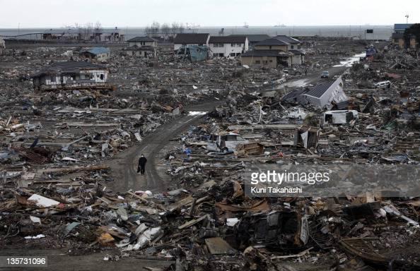 A man walks in Kadonowakicyo after massive earthquake and tsunami hit northern Japan March 26 2011 in Ishinomaki Miyagi Japan More than 10000 were...