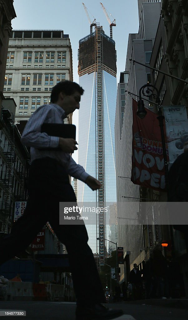 A man walks in Lower Manhattan as One World Trade Center (C) rises under construction on October 22, 2012 in New York City. The Census Bureau reported last month that between 2000 and 2010 the downtown population grew by nearly 40,000 people, in spite of the September 11 terrorist attacks at the World Trade Center. One World Trade Center is scheduled to open in 2014 at the symbolic height of 1,776 feet and will be the tallest building in the Western Hemisphere.