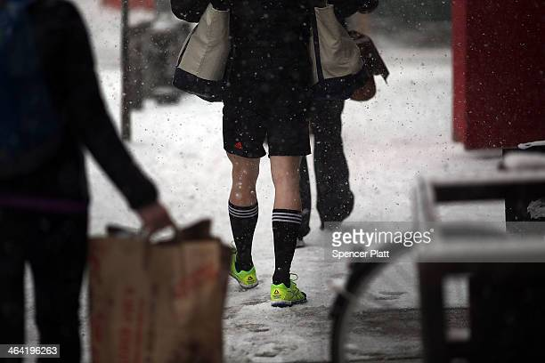 A man walks in shorts in Manhattan during a snowstorm that is moving through the Northeast on January 21 2014 in New York City Along with dropping...