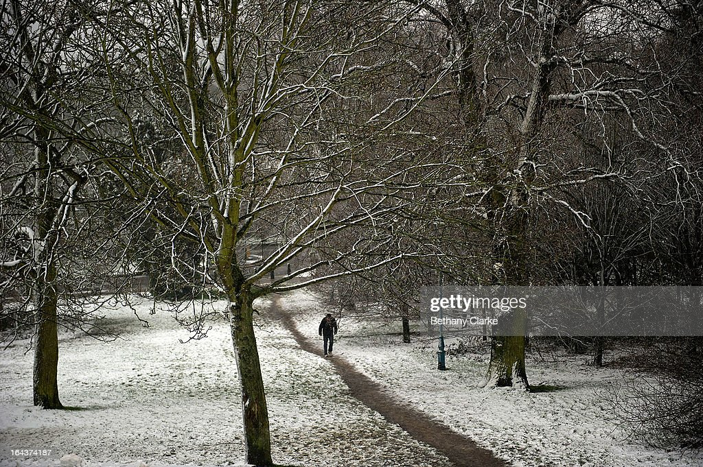 A man walks in snow covered Alexandra Park on March 23, 2013 in London, United Kingdom. The UK is facing another day of severe weather disruption, with flood and snow warnings issued in a number of regions across the country.