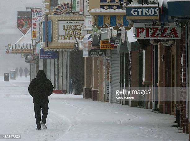 A man walks in the cold weather along the snow covered Atlantic City boardwalk on January 27 2015 in Atlantic City New Jersey Much of the Northeast...