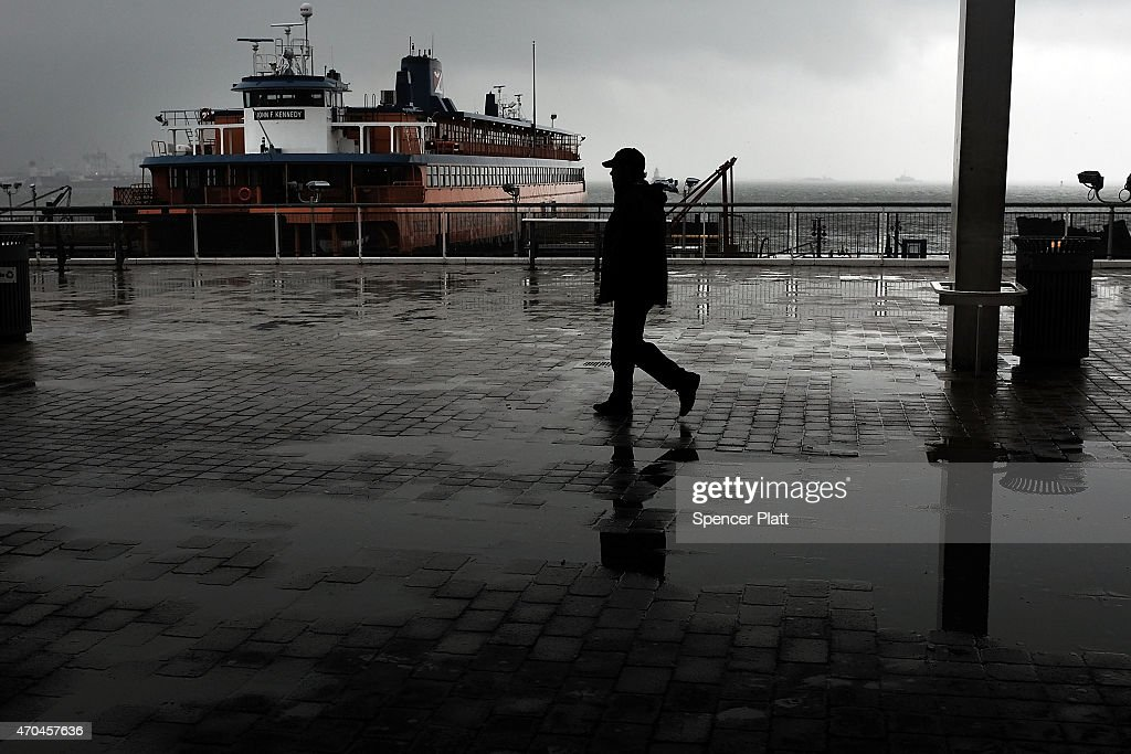 A man walks in the rain at the Staten Island Ferry terminal in Staten Island on April 20 2015 in New York City Much of the East Coast experienced...