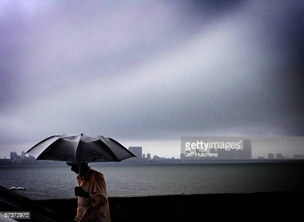 A man walks in the rain with a umbrella on September 09 2005 in Mumbai India Emerging from one of the most deadly monsoon seasons in recent history...