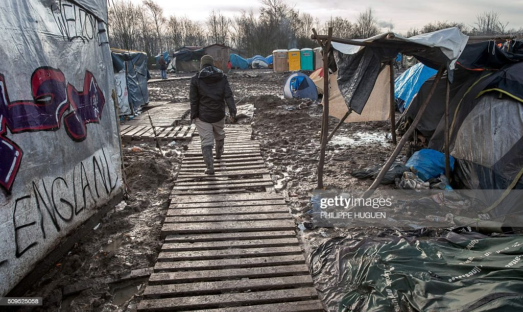A man walks in the so-called 'Jungle' migrant camp in Gande-Synthe where 2,500 refugees from Kurdistan, Iraq and Syria live on February 11, 2016 in Grande-Synthe near the city of Dunkirk, northern France. / AFP / PHILIPPE HUGUEN