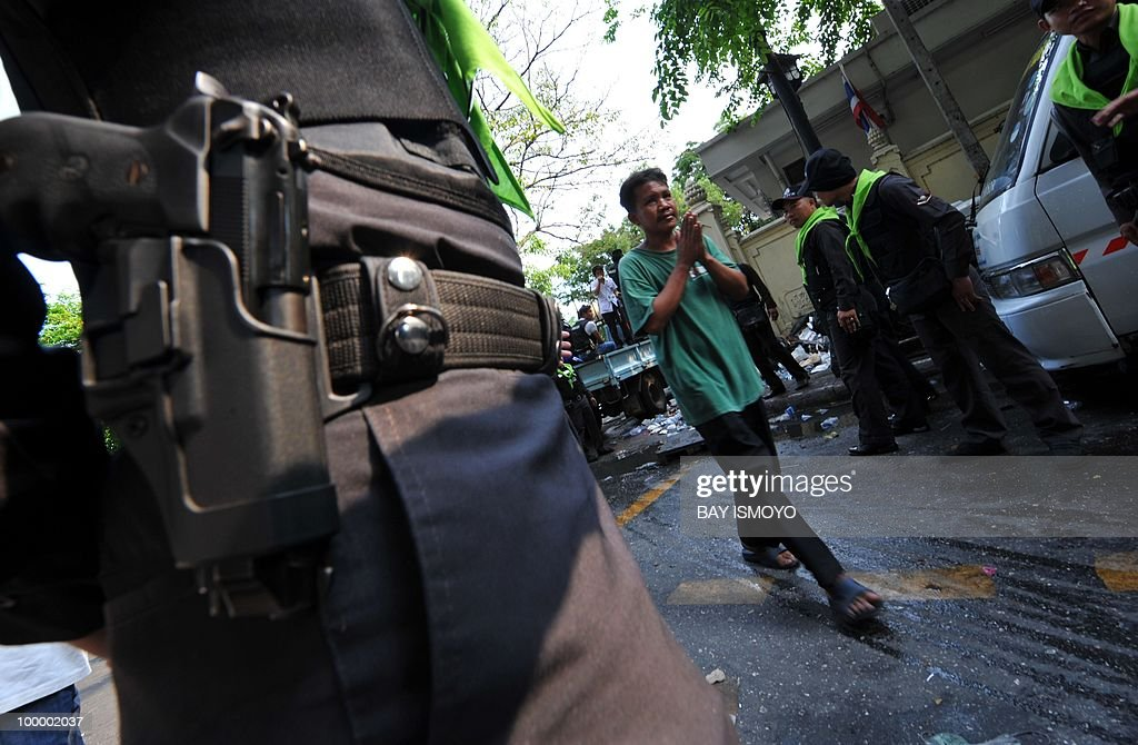 A man walks inside a cordon of policemen from a temple declared a 'safe zone' in the heart of a Thai anti-government rally site towards the Police headquarters of Bangkok across the street in downtown Bangkok on May 20, 2010. Several people were killed on May 19, 2010 in clashes at a temple declared a 'safe zone' in the heart of a Thai anti-government rally site that was shut down in a military offensive, police said Thursday.