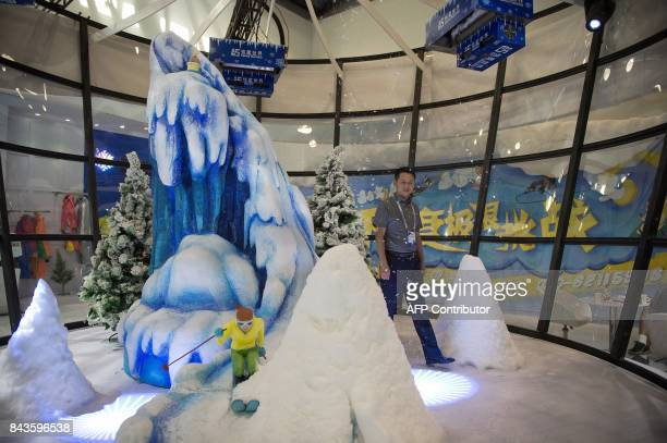 A man walks inside a stand where snow machines create snow flakes at the China National Convention Centre during the World Winter Sports Expo in...