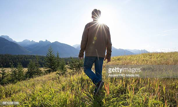 Man walks into mountain meadow at sunrise