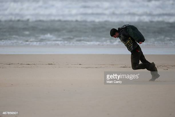 A man walks into the strong winds on the beach on February 8 2014 in Hayle Cornwall England The UK is bracing itself for more storms and spells of...