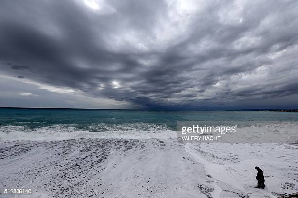 TOPSHOT A man walks into the water as waves crash onto the shore of the Mediterranean sea in Nice on February 28 2016 / AFP / VALERY HACHE