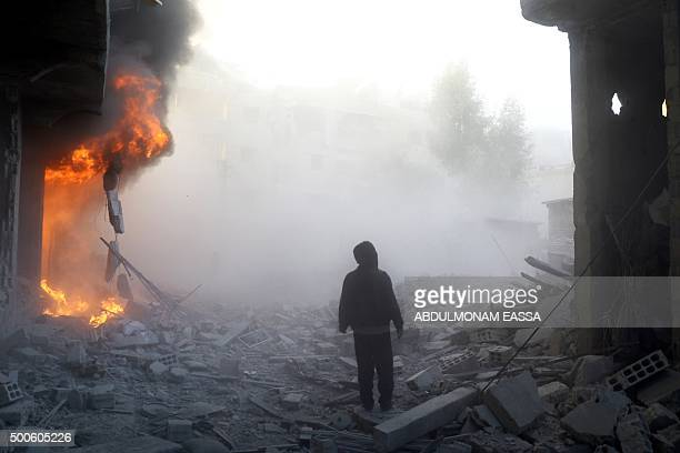TOPSHOT A man walks near a building on fire following a reported air strike by government forces in the rebelheld region of Eastern Ghouta on the...