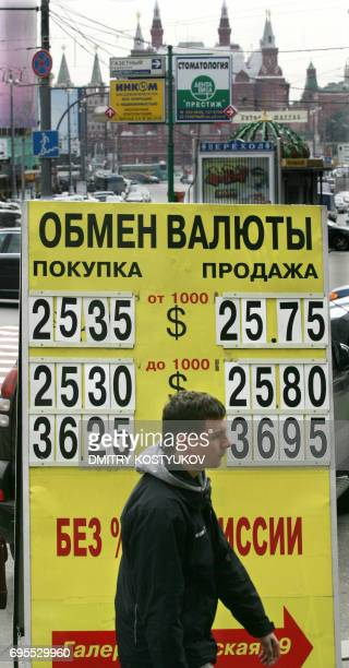 A man walks near a currency exchange office billboard in central Moscow on September 19 2008 Trading was suspended Friday on Russian stock markets...