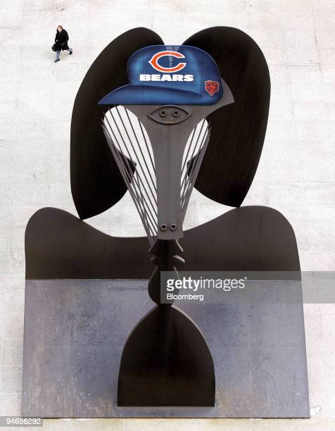 A man walks near a Picasso art sculpture which has been fitted with a Chicago Bears cap in Daley Plaza in Chicago Illinois Friday Feb 2 2007 The...
