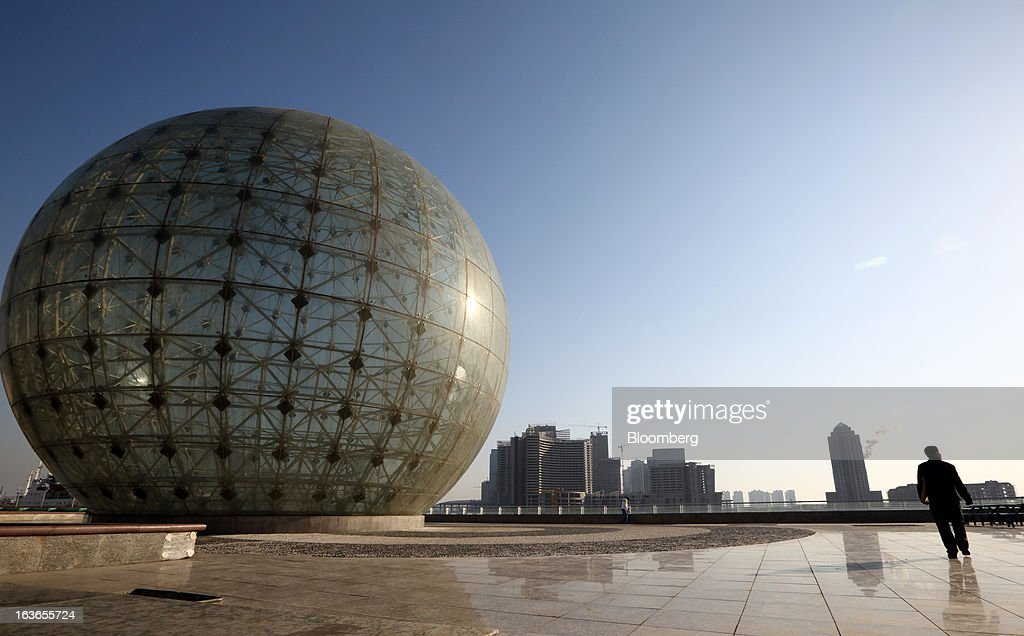 A man walks near a spherical monument by the waterfront in Tianjin, China, on Wednesday, March 13, 2013. China's money-market rate rose to a one-week high after central bank Governor Zhou Xiaochuan said yesterday the nation should be on 'high alert' over inflation. Photographer: Tomohiro Ohsumi/Bloomberg via Getty Images