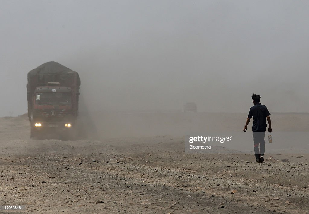 A man walks near a truck carrying coal at a reloading facility on the border with China in South Gobi, Mongolia, on Thursday, June 6, 2013. Mongolia, a country of almost 2.9 million people, has some of the world's biggest undeveloped mineral reserves, including Oyu Tolgoi, a copper and gold mine, and Tavan Tolgoi, a coal deposit. Photographer: Tomohiro Ohsumi/Bloomberg via Getty Images