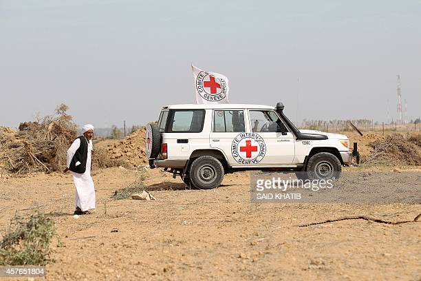A man walks near an International Committee of the Red Cross vehicle as the comittee assists Palestinian farmers to repair their fields that were...