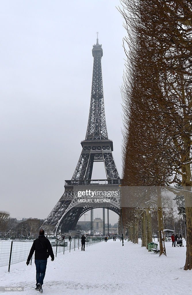 A man walks near the Eiffel tower on January 19, 2013 in Paris, after the snow fell over the French capital overnight.