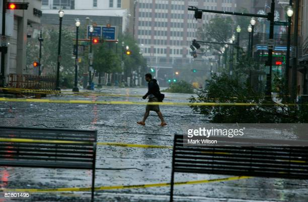 A man walks near the JP Morgan Chase Tower which had many windows blown out when Hurricane Ike passed through the city September 13 2008 in Houston...