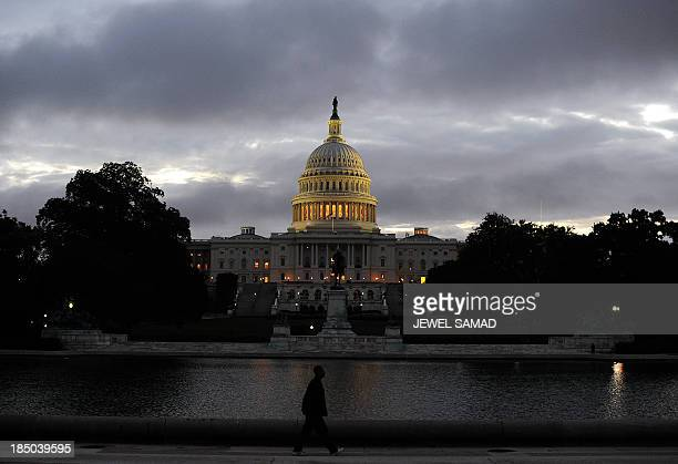 A man walks near the US Capitol building before sunrise on the morning after a bipartisan bill was passed by the House and the Senate to reopen the...
