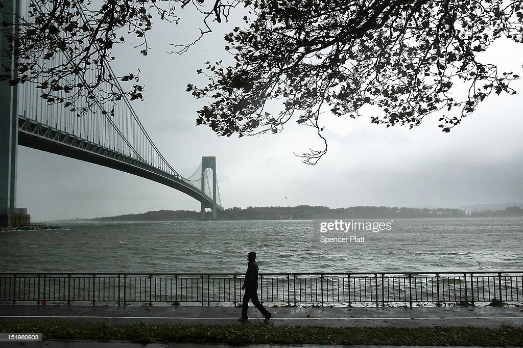 A man walks near the Verrazano Bridge as Hurricane Sandy begins to affect the area on October 29, 2012 in the in Brooklyn borough of New York City. The storm, which threatens 50 million people in the eastern third of the U.S., is expected to bring days of rain, high winds and possibly heavy snow. New York Governor Andrew Cuomo announced the closure of all New York City bus, subway and commuter rail service as of Sunday evening.