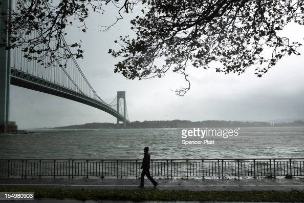 A man walks near the Verrazano Bridge as Hurricane Sandy begins to affect the area on October 29 2012 in the in Brooklyn borough of New York City The...