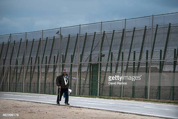 A man walks next the border fence that limits Morocco from the Spanish enclave of Melilla on January 22 2015 in Melilla Spain According to Spanish...