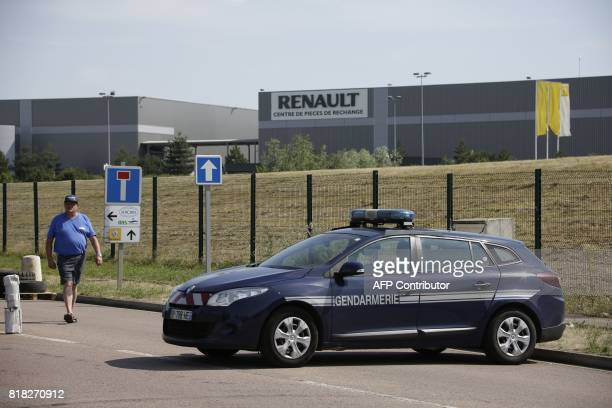 A man walks next to a French gendarmerie car as employees of French auto parts manufacturer GMS threatened with liquidation block the site of their...