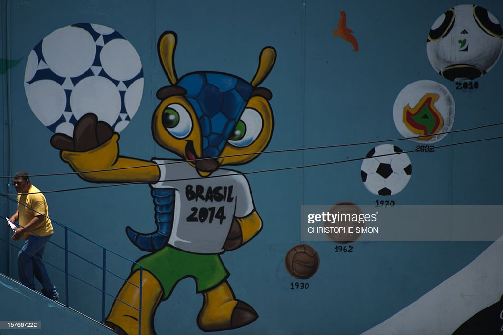 A man walks next to a mural depicting 'Fuleco', the mascot of the Brazil 2014 FIFA World Cup, at the Maracana tube station, next to the Maracana stadium under works, in Rio de Janeiro, Brazil on December 5, 2012.