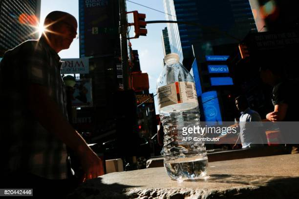 A man walks next to a near empty bottle of water in Times Square during a sunny day as hot temperatures continue in New York on July 21 2017 / AFP...
