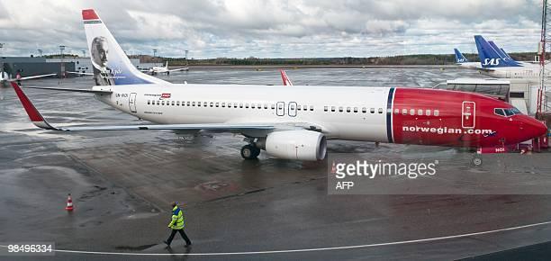A man walks next to a Norwegian Boeing 737800 aircraft at at the normaly busy tarmac at Terminal 4 at Arlanda Airport outside Stockholm on April 16...