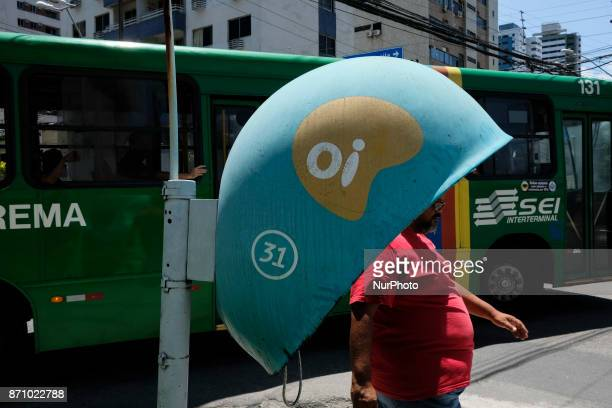A man walks next to a public telephone of the Brazilian telephone operator Oi SA in the city of Recife in the Northeast of Brazil on November 6 2017...