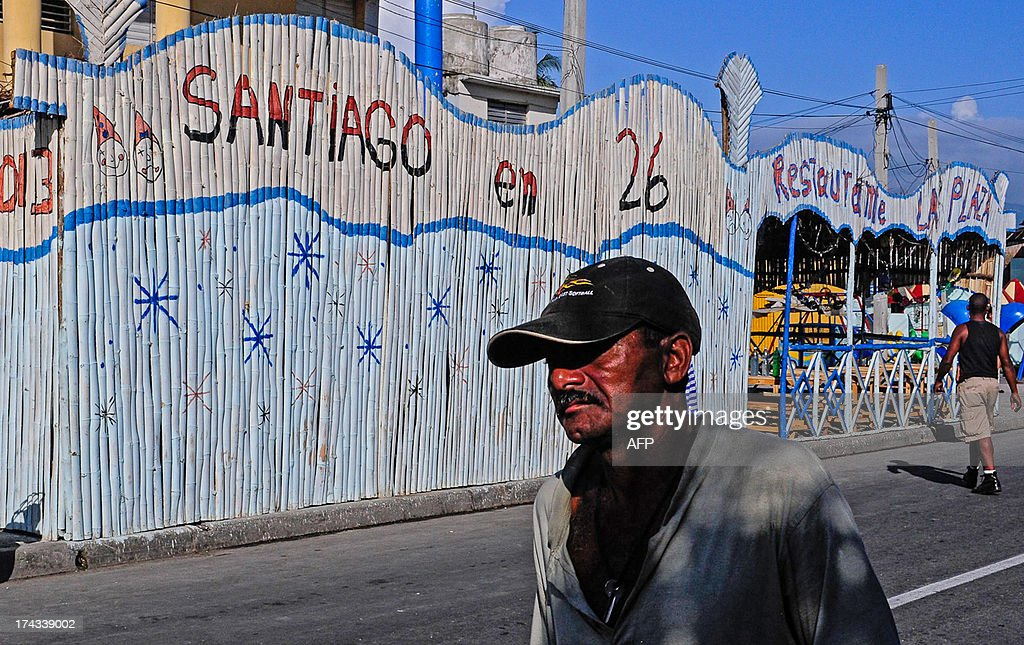 A man walks next to a restaurant called 'Santiago en 26', referring to July 26, 1953, the date in which the Moncada Barracks was attacked by a group of revolutionaries led by Fidel Castro, in Santiago de Cuba, on July 24, 2013. On July 26, 2013 will be the 60th anniversary of the attack, which is considered as the beginning of the Cuban Revolution