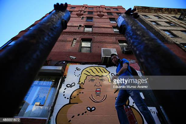 A man walks next to an AntiDonald Trump mural painted on a building in Lower Manhattan on August 28 2015 in New York City Trump is leading the...