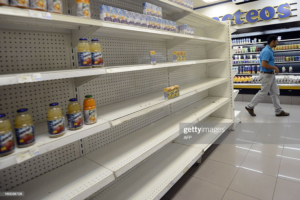 A man walks next to empty shelves in a supermarket in Caracas on January 22, 2012. According to the Central Bank (BCV) shortage of goods reached 16.3% in December 2012, the highest number in the last four years. AFP PHOTO / Leo RAMIREZ