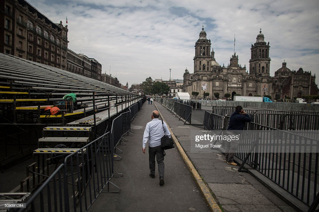 A man walks next to fences installed at Zocalo Main Square on February 10, 2016 in Mexico City, Mexico. The Zocalo main square is closed to public, as the perimeter is prepared for the upcoming visit of Pope Francis on February 12-17.