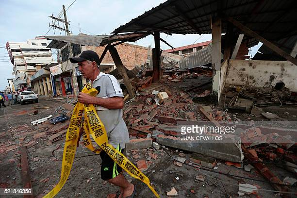 A man walks next to rubble at a street after a 78magnitude quake in Portoviejo Ecuador on April 17 2016 At least 77 people were killed when a...