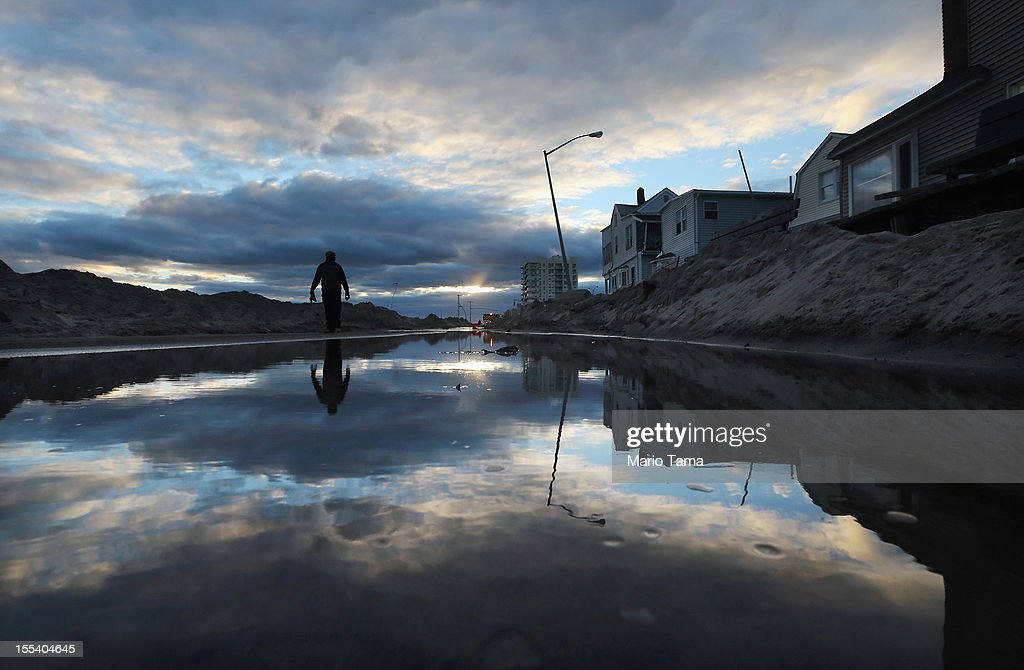 A man walks next to standing water and piles of sand swept onto a road from Superstorm Sandy at Rockaway Beach on November 3, 2012 in the Queens borough of New York City. Most of the Rockaway Peninsula remains without power. With the death toll currently over 90 and millions of homes and businesses without power, the US east coast is attempting to recover from the effects of floods, fires and power outages brought on by Superstorm Sandy.
