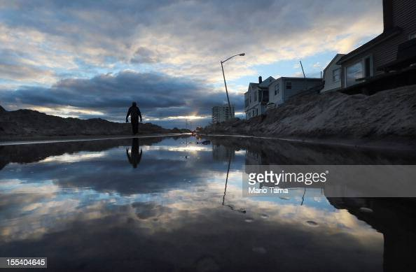 A man walks next to standing water and piles of sand swept onto a road from Superstorm Sandy at Rockaway Beach on November 3 2012 in the Queens...